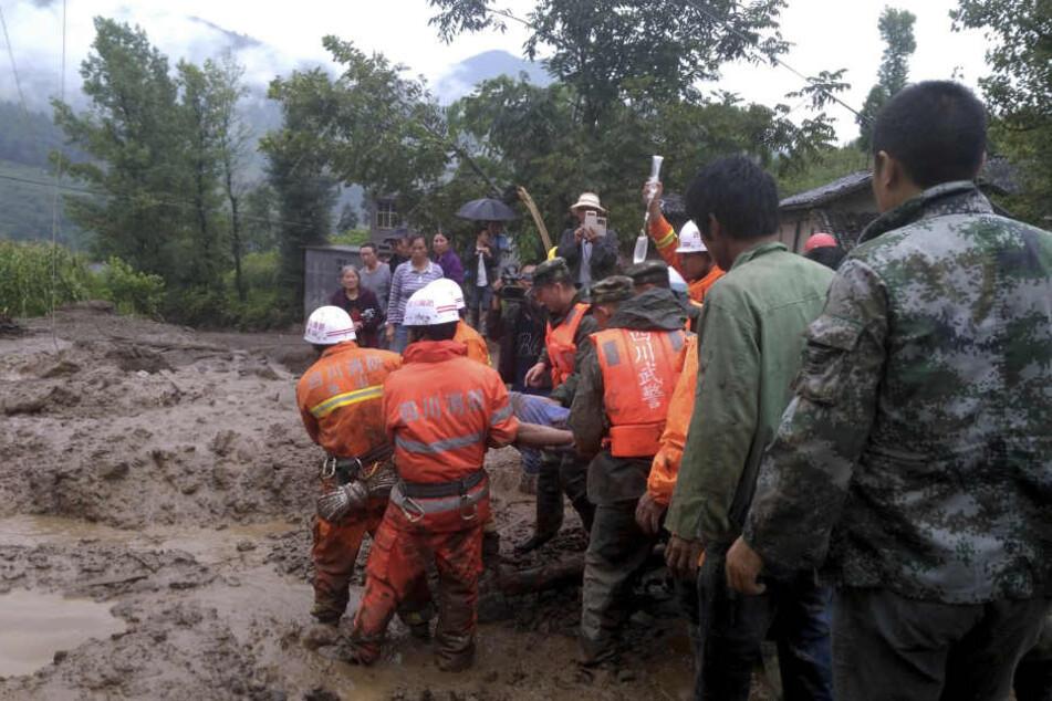 Rettungskräfte tragen am 08.08.2017 in Gengdi (China) einen Mann, der bei einem Erdrutsch verletzt wurde. Durch schwere Regenfälle war der Erdrutsch ausgelöst worden, der möglicherweise mehr als 20 Menschen das Leben kostete.