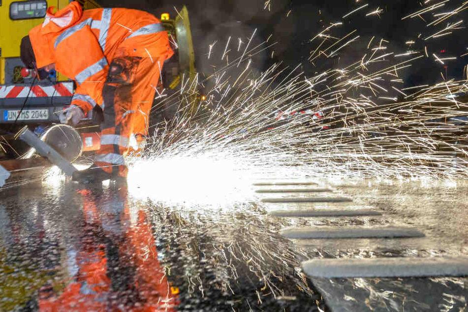 Ein Bauarbeiter zerflext das gebrochene Lamellenstück auf der A7 bei Hamburg-Waltershof.