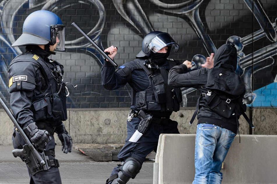 Ein Polizist geht während der Demo in Halle (Saale) mit seinem Schlagstock gegen einen linken Demonstranten vor.