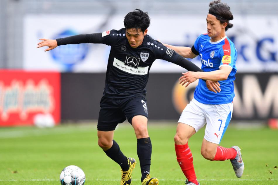 Wataru Endo (27, links) vom VfB Stuttgart und Jae-sung Lee von Holstein Kiel kämpfen um den Ball.