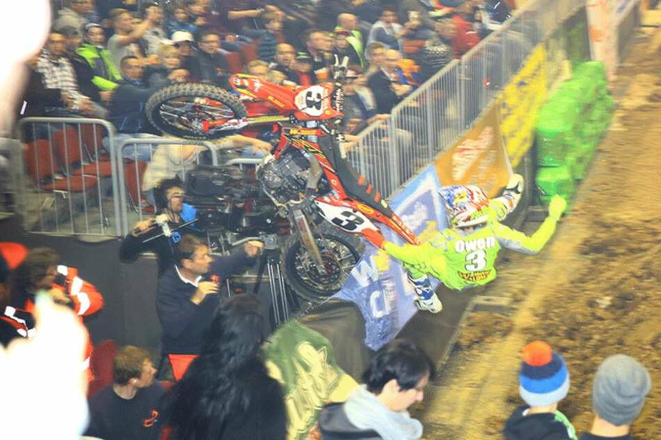 Das Motorrad fliegt über die Bande auf den dort stehenden Kameramann zu.