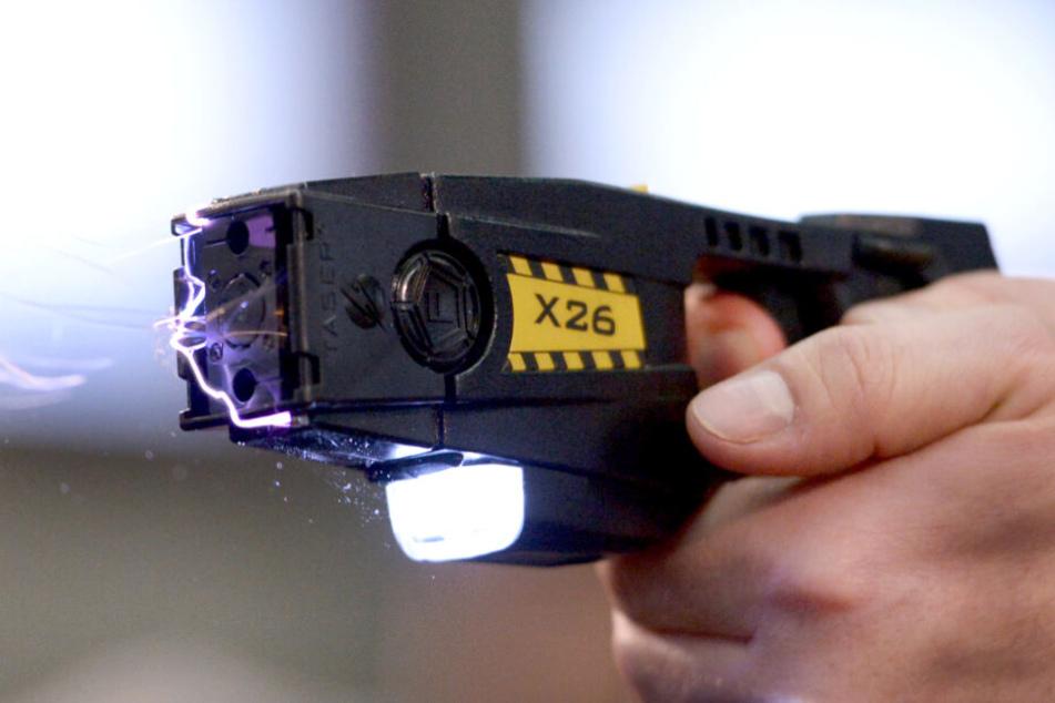 Ein Taser verschiesst Pfeile, die über dünne Drähte mit der Waffe verbunden sind und über die Strom mit etwa 50.000 Volt fließt.