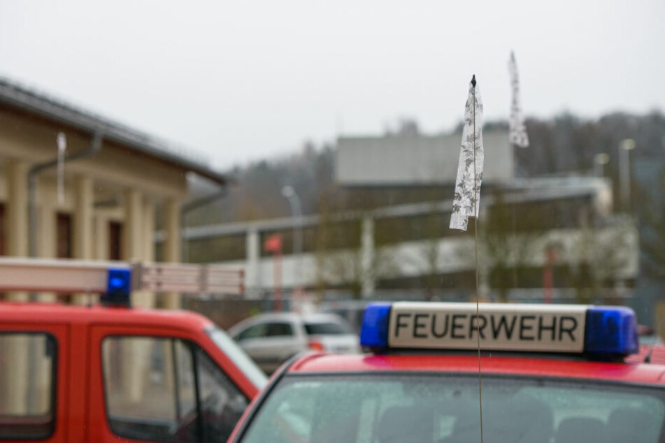 An den Fahrzeugen der Feuerwehr sind Trauerflore angebracht.