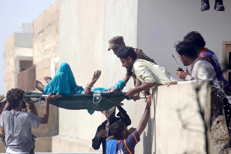 Freiwillige tragen einen Verletzten auf einer Liege.