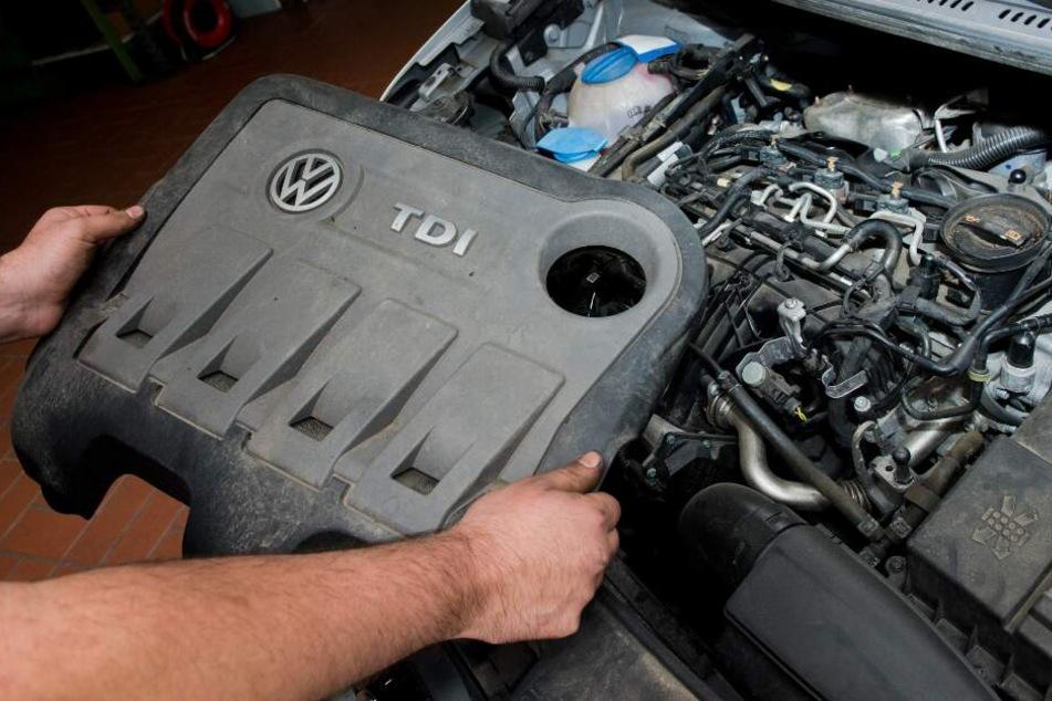 Ein KFZ-Servicetechniker hält die Abdeckung vor einen vom Abgas-Skandal betroffenen 2.0l TDI Dieselmotor vom Typ EA189.
