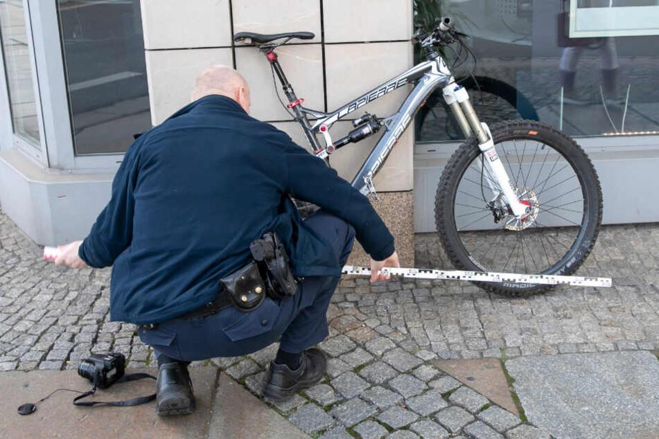 Ein Beamter nimmt Messungen am Unfall-Rad vor.