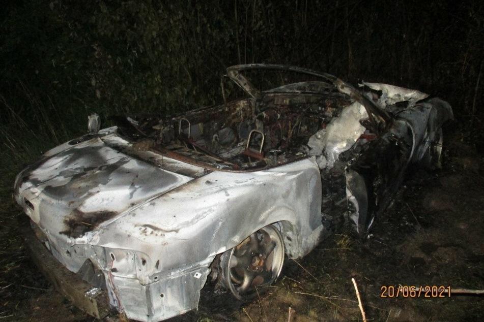 Nach einem Unfall war der ursprünglich grüne Mazda MX-5 im hohen Gras abseits der Straße abgestellt worden und brannte vollständig aus.