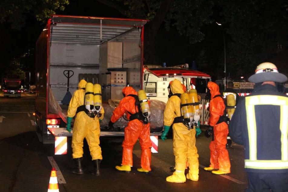 Feuerwehrleute in Schutzanzügen bringen die Leiche zum Lkw.