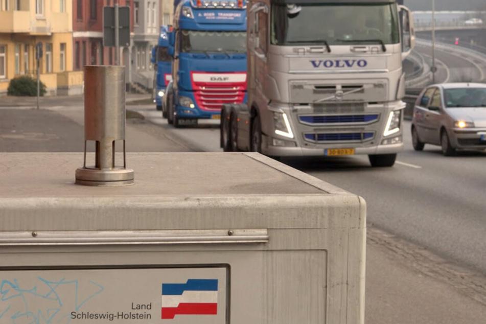 Fahrzeuge fahren an einer Luftmessstation am Theoder-Heuss-Ring in Kiel vorbei.