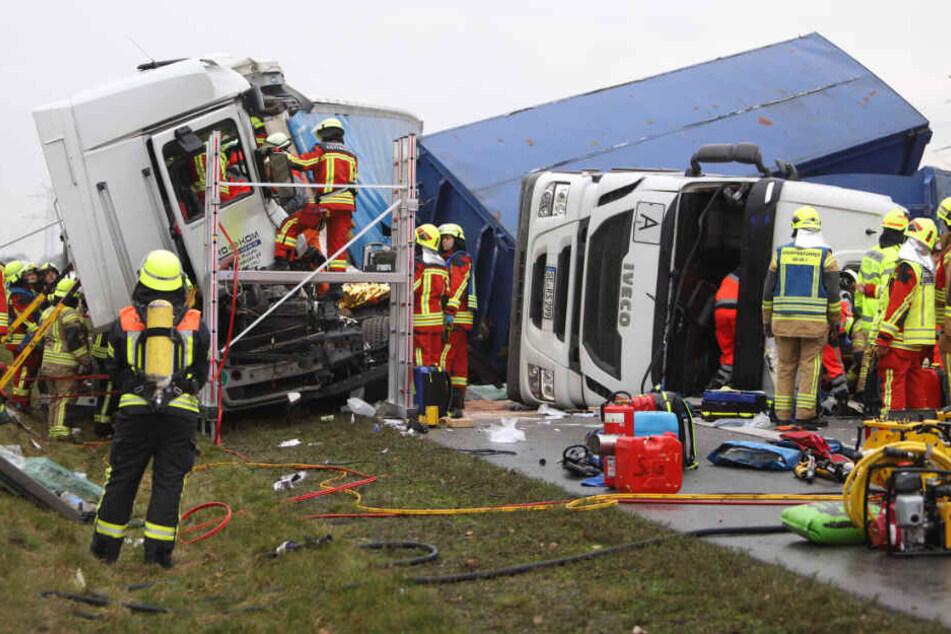 Die Einsatzkräfte bergen die eingeklemmten Fahrer aus ihren Fahrzeugen.