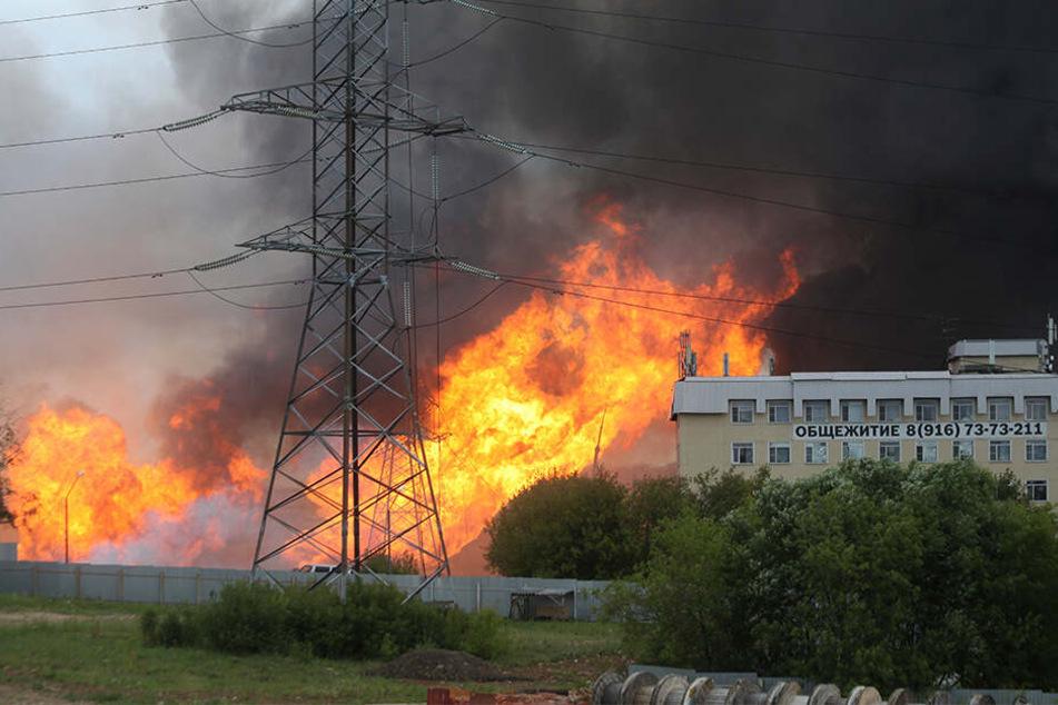 Schwarzer Rauch und Flammen steigen in der Nähe eines Wärmekraftwerks auf.