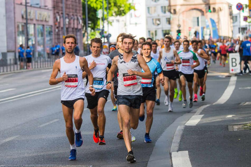 Die Spitzengruppe läuft kurz nach dem Start über die Eschersheimer Landstraße mit dem Eschenheimer Tor im Hintergrund. In der Innenstadt der Mainmetropole findet der Firmenlauf J.P. Morgan Corporate Challenge statt.