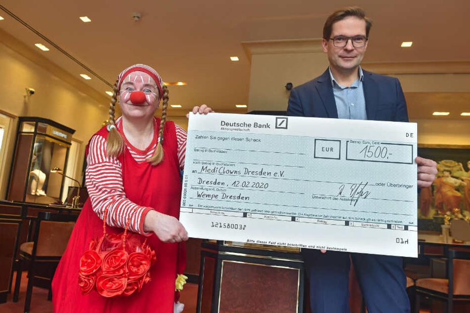 Pampolina (Ute Gilles, 52) nimmt freudestrahlend einen Scheck von Wempe-Geschäftsführer Ralf Pfeiffer (49) entgegen.