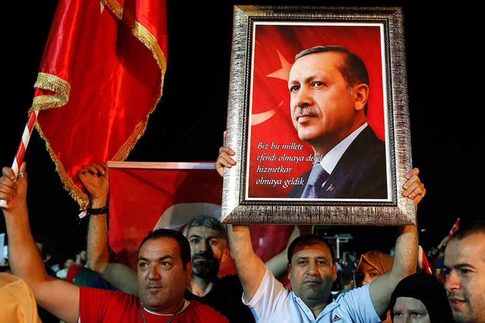 Anhänger halten ein Bild von Repec Tayyip Erdogan (64) hoch.