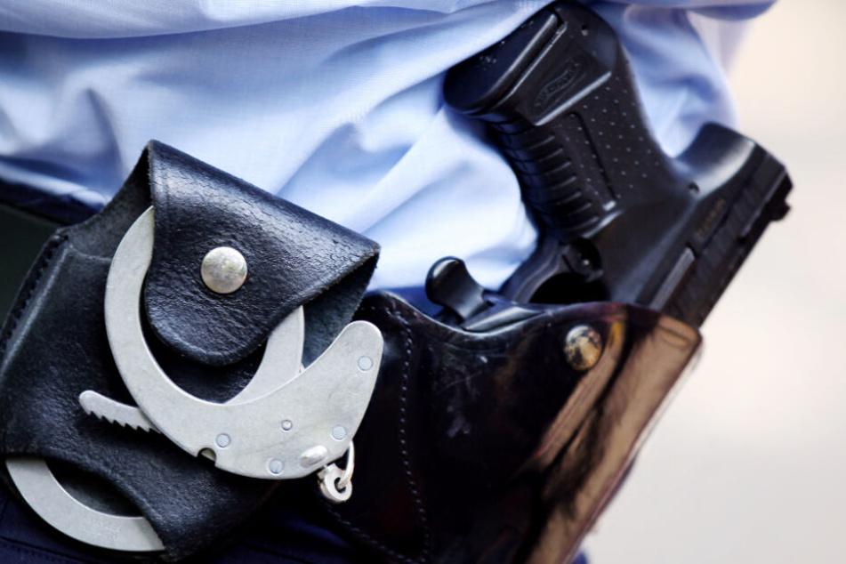 Mann mit Baby auf dem Schoss bedroht Frau mit Schusswaffe