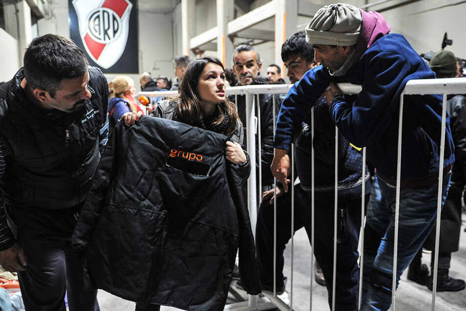 Eine Freiwillige bietet im Monumental Stadion den Obdachlosen warme Kleidung an.