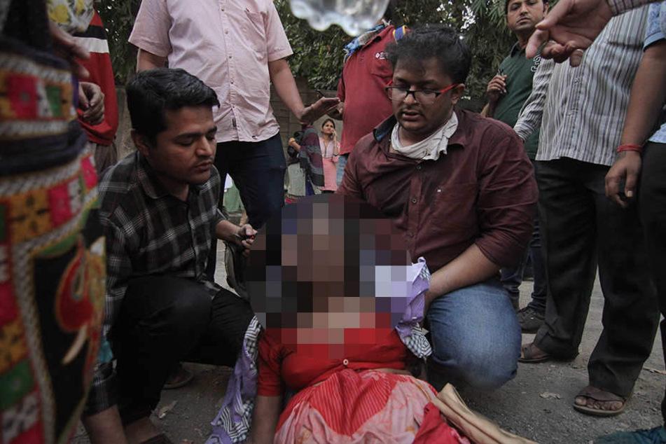 Eine verletzte Frau wird nach ihrer Rettung aus dem brennenden ESIC Kamgar Krankenhaus betreut.