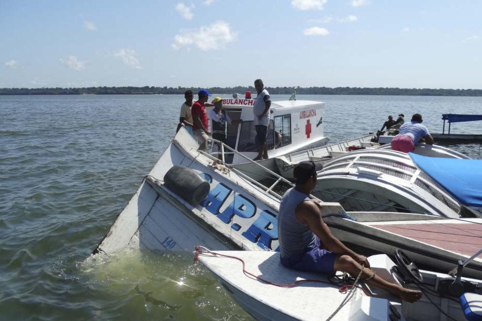 """Ein Rettungsboot nähert sich dem gesunkenen Schiff """"Comandante Ribeiro""""."""