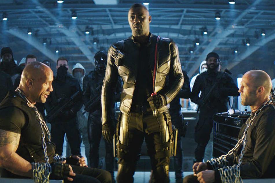 Der neue Superschurke Brixton (M., Idris Elba) hat Luke Hobbs (l., Dwayne Johnson) und Deckard Shaw (r., Jason Statham) in seiner Gewalt.