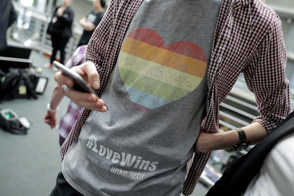 """Ein Mitarbeiter eines Bundestagsabgeordneten der Linken trägt ein T-Shirt mit einem Herz in Regenbogenfarben und dem Titel """"#LoveWins""""."""