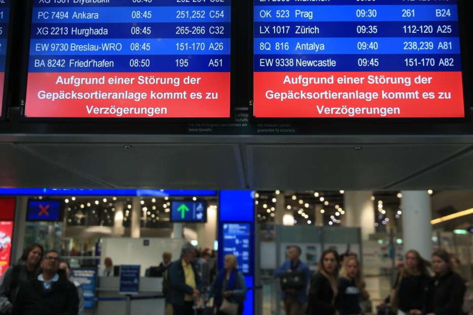 Hinweistafeln im Düsseldorfer Flughafen zeigen an, dass es aufgrund einer Störung der Gepäcksortierungsanlage zu Verzögerungen kommt.