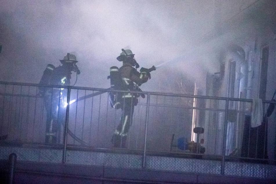 Einsatzkräfte in Atemschutzausrüstung kämpfen gegen den Brand an.