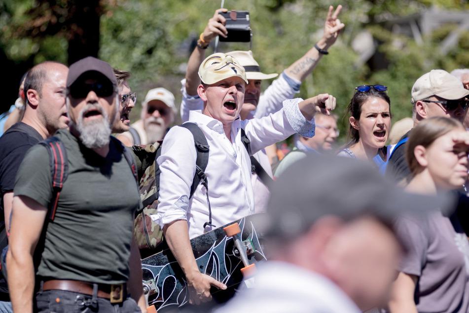 Teilnehmer der Demonstration gegen die Corona-Beschränkungen rufen Slogans.