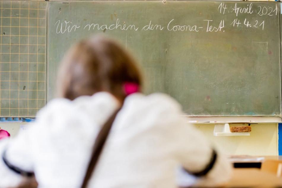 """Eine Schülerin sitzt bei einem Probelauf mit Corona-Schnelltests an der Grundschule in der Köllnischen Heide in Berlin-Neukölln vor einer Tafel mit der Aufschrift """"Wir machen den Corona-Test""""."""