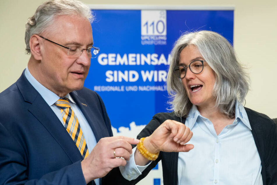 """Joachim Herrmann (CSU), Innenminister von Bayern, betrachtet am Hangelenk von Katharina Werner, Projektleiterin für das Upcycling alter Polizeiuniformen bei den Barmherzigen Brüdern, """"Knöpfe-Armband"""" bestehend aus Hemdknöpfen alter Polizeiuniformen."""