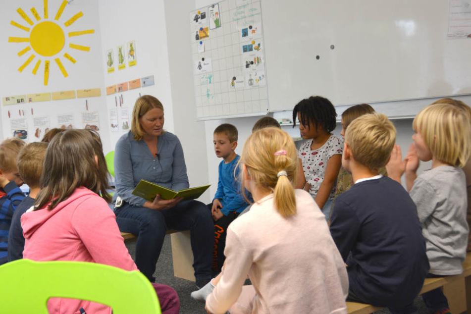 Die Lehrerin Anne Braun von der Padua Schule sitzt inmitten der Kinder während des Unterrichts.
