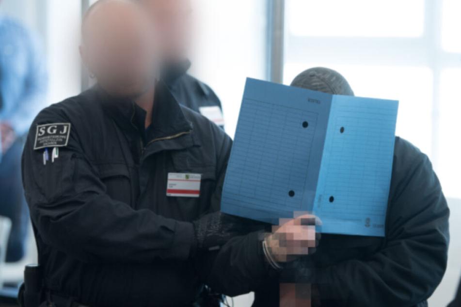 """Ein Angeklagter im Prozess gegen die selbsternannte """"Revolution Chemnitz"""" wird im Prozessgebäude des Oberlandesgerichts Dresden zu Prozessbeginn in den Verhandlungssaal geführt. Die insgesamt acht Männer zwischen 21 und 32 Jahren sind wegen Bildung einer"""