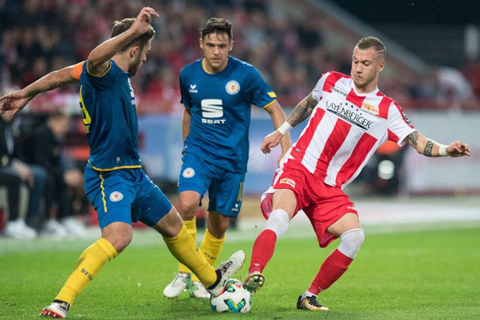 Braunschweigs Ken Reichel (l), Braunschweigs Mirko Boland (M) und Unions Marcel Hartel gehen gemeinsam zum Ball.