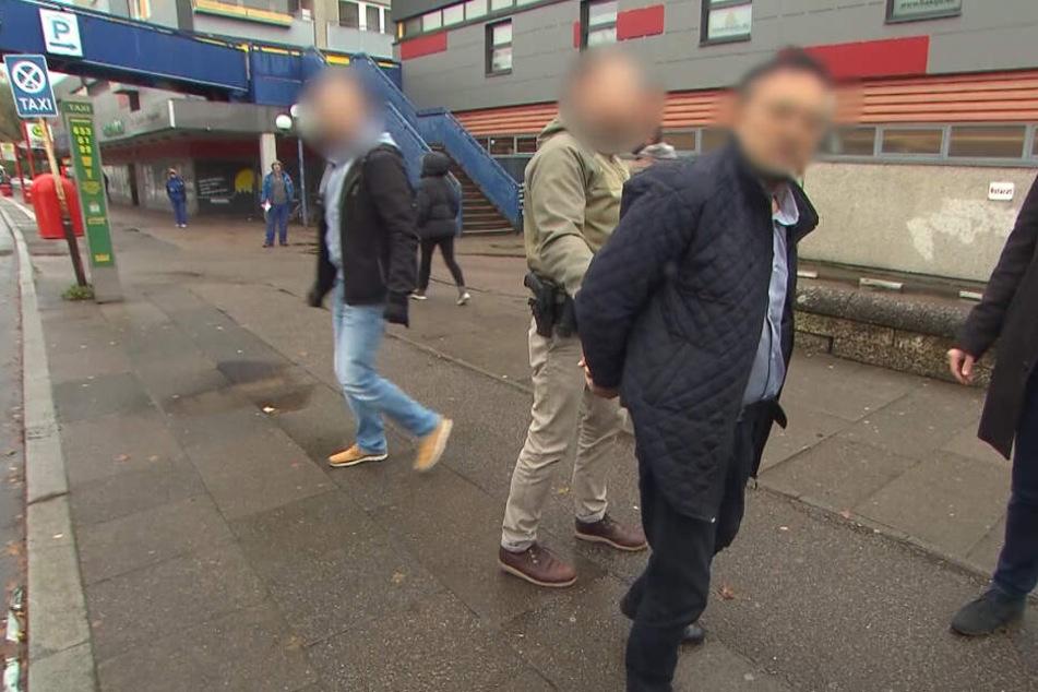 Polizeibeamte führten den Verdächtigen in Handschellen ab.