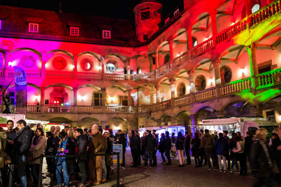 Menschen besuchen bei der Langen Nacht der Museen vor zwei Jahren das bunt angestrahlte Landesmuseum Baden-Württemberg.