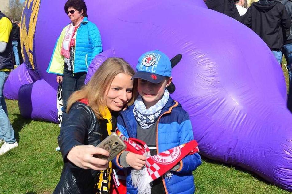 Fans posierten für Erinnerungsfotos vorm lila Aue-Schwein.