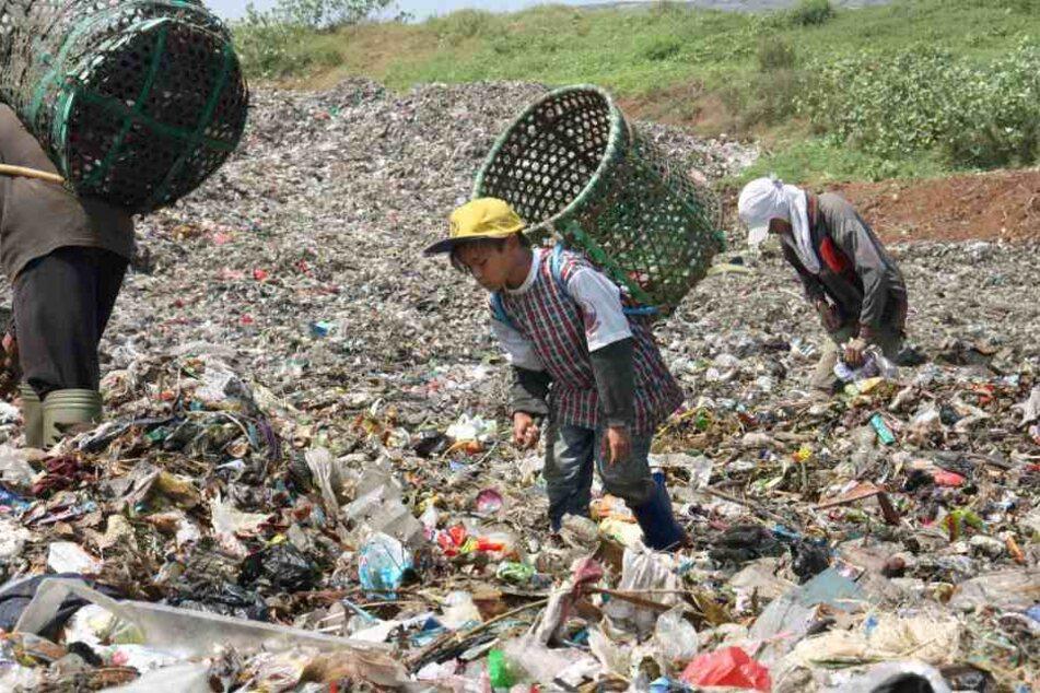 Ein Junge sucht in Jakarta nach Dingen im Müll, die sich weiterverkaufen lassen.