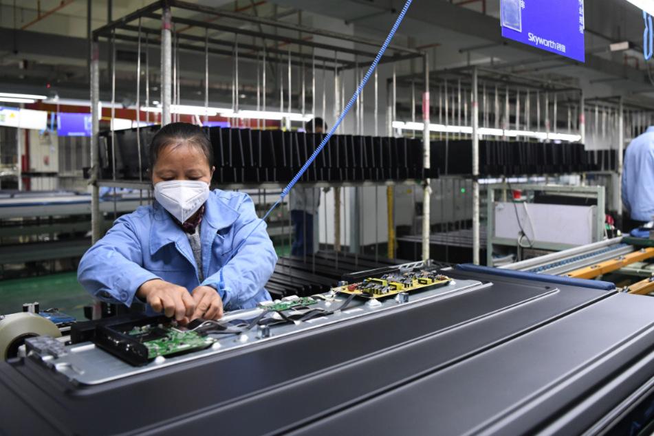 Angestellte arbeiten mit Mundschutz in einer Fernseherfabrik von Skyworth.