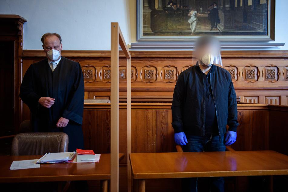 Der Angeklagte (r.) steht im Gerichtssaal neben seinem Anwalt. Dem 47-jährigen Mann wird die Vergewaltigung und Ermordung seiner Ehefrau vorgeworfen.