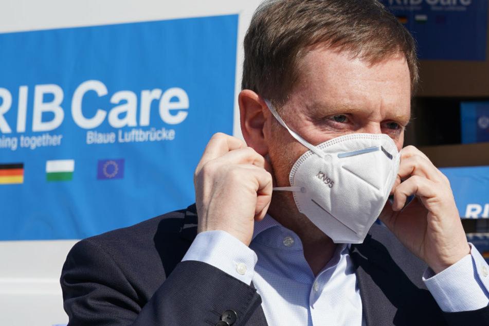 Ministerpräsident Michael Kretschmer setzt sich einen Mundschutz auf.