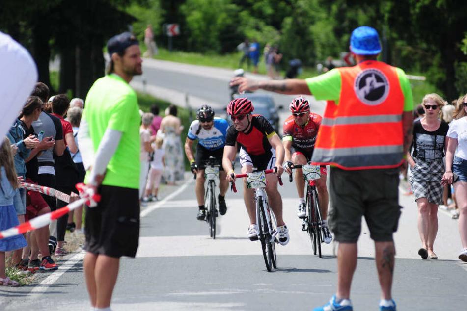Beim Fichtelberg-Radmarathon von Chemnitz auf den höchsten Berg Sachsens sichert ein Helfer die Strecke.