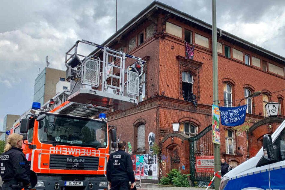 Einsatzkräfte von Polizei und Feuerwehr stehen im Bezirk Friedrichshain vor einem leerstehenden Industriegebäude, in das Unbekannte mit Kletterausrüstung eingedrungen waren und es besetzt haben.