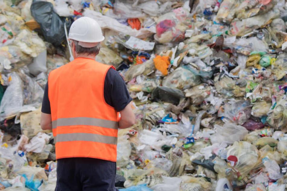 Ein Mann steht vor einem Müllberg auf einer Deponie. (Archivbild)