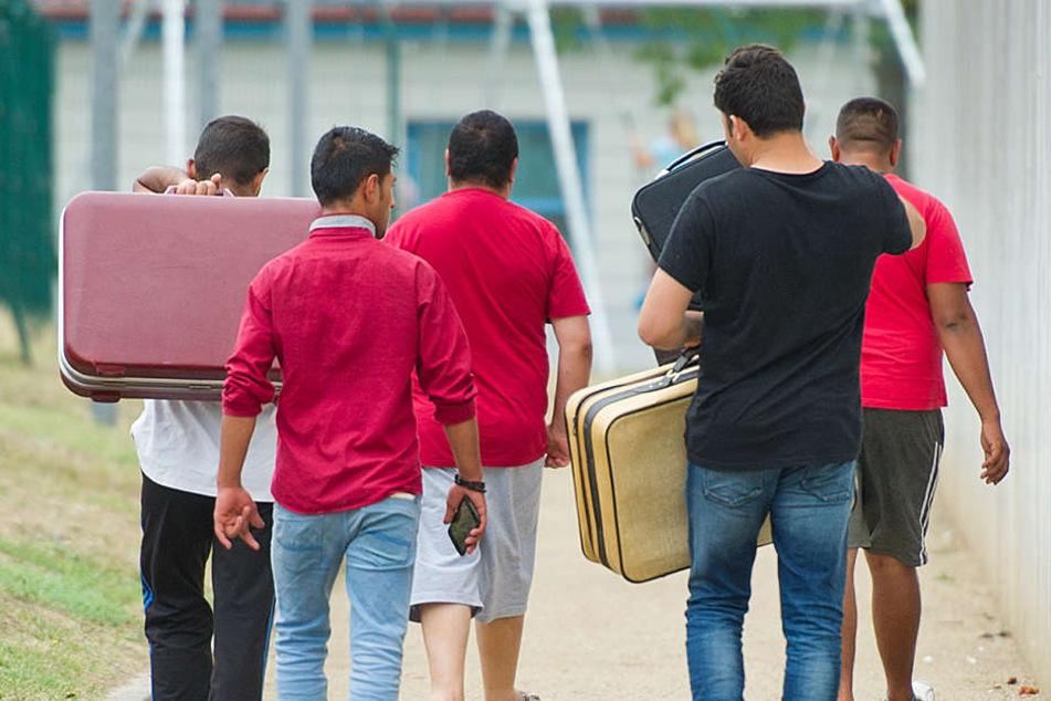 Flüchtlinge laufen mit Koffern bepackt auf einem Weg einer Erstaufnahmeeinrichtung für Flüchtlinge.