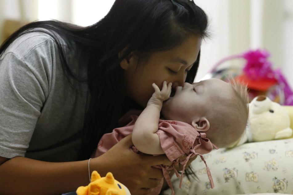 Eine Mutter küsst ihr Baby mit Down-Syndrom (Symbolbild)