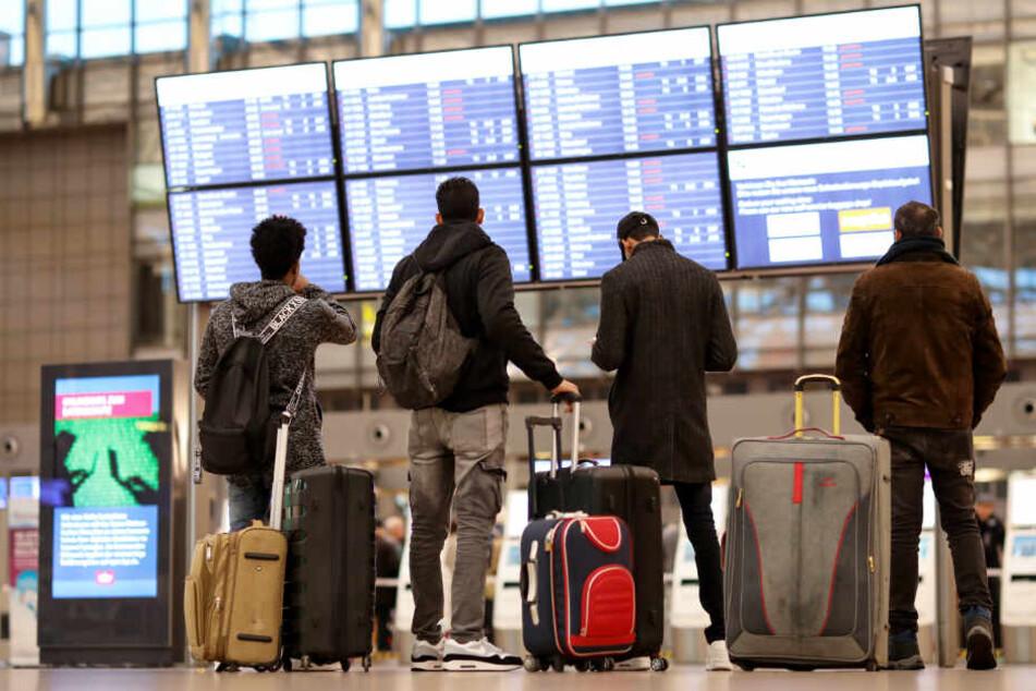 Reisende stehen am Flughafen Hamburg und informieren sich über die Abflüge und Ankünfte. Donnerstag dürften viele Flüge ausfallen.