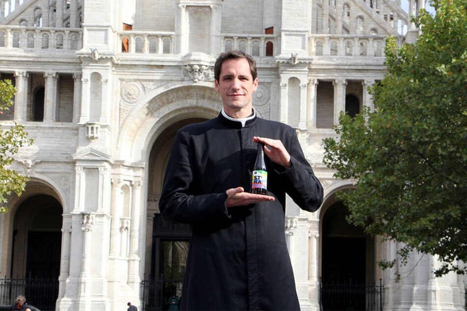 """Pfarrer Jeremie Schaub steht mit einer Flasche """"Ste Kat"""" Craft Beer vor """"seiner"""" Kirche."""