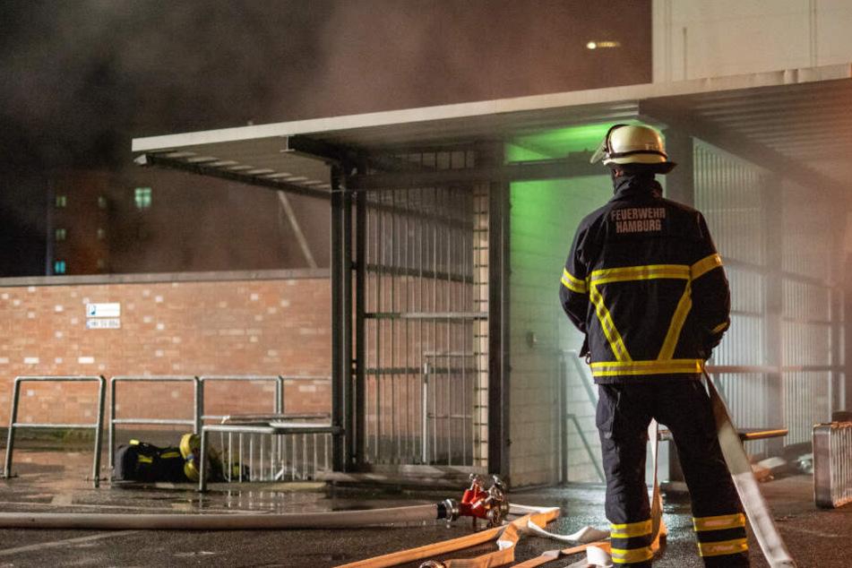 Ein Feuerwehrmann steht vor einem Aufgang der verqualmten Tiefgarage.