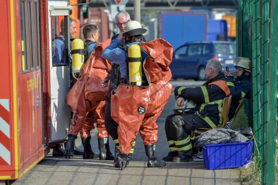 Feuerwehrmänner legen spezielle und vor allem gegen Chemikalien extrem resistente Schutzanzüge an, um den Brand nach dem Chemieunfall zu bekämpfen.