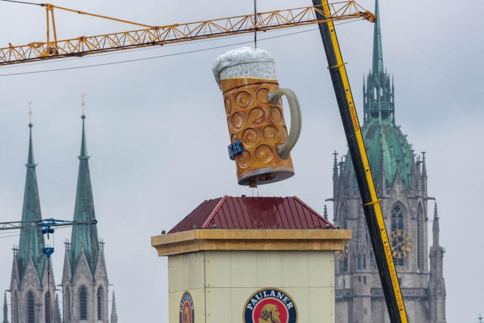Ein übergroßer und rund rund 1,5 Tonnen schwerer Bierkrug wird mit einem Kran auf der Theresienwiese an seinen Platz gehoben. Im Hintergrund ist die Sankt Paul Kirche zu sehen.