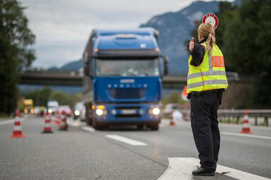 Eine Polizistin winkt an der Anschlussstelle Bad Reichenhall der Autobahn A8 von Salzburg nach München ein Fahrzeug in die Grenzkontrollstelle.